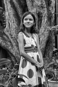 girl in polka dot dress by tree